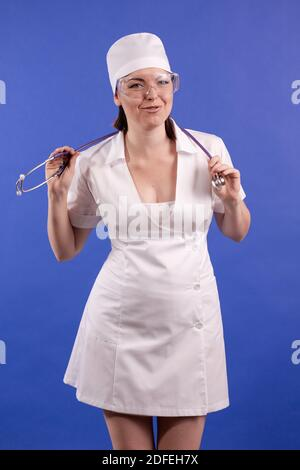 mujer joven doctor en un abrigo blanco y sombrero posando sobre un fondo azul