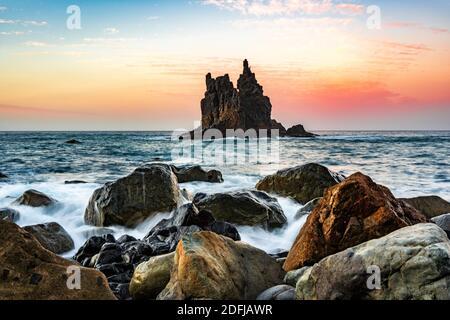 puesta de sol en la playa con olas y la isla de roca en el mar en tenerife