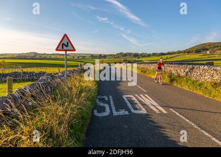 Vista de muros de piedra seca y ciclista en el carril del país, foulow, Derbyshire Peak District, Inglaterra, Reino Unido, Europa