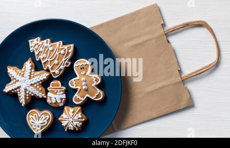 Ponga galletas festivas de año Nuevo en un plato azul sobre fondo blanco de madera con bolsa de la compra, concepto de entrega.