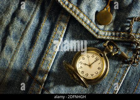 El reloj de bolsillo Vintage se coloca sobre una vieja camisa azul de denim y el sol de la mañana brilla en la esquina superior derecha. El concepto de la importancia del tiempo. C Foto de stock