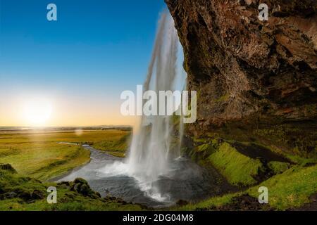 Vista a través de la cascada Seljalandsfoss en Islandia al atardecer