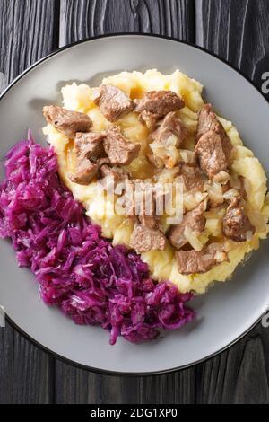 Hachee Dutch Beef and Onion Stew servido con puré de patatas, repollo rojo estofado primer plano en el plato de la mesa. Vista superior vertical desde arriba