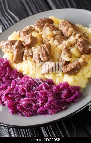 Hachee Dutch Beef and Onion Stew servido con puré de patatas, repollo rojo estofado primer plano en el plato sobre la mesa. Vertical