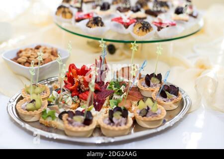 El buffet en la recepción. Surtido de canapés en una mesa. Servicio de banquetes. Comida de catering, aperitivos con diferentes tipos de queso, jamón, salami, pro Foto de stock