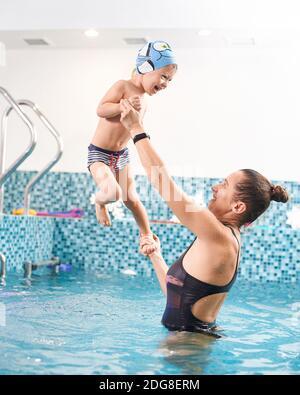 Madre apoyando a su hijo pequeño en la piscina sobre agua azul. Niño feliz pasando un rato estupendo con su mamá en el agua, usando gorro de baño y bañadores. Concepto de familia sana