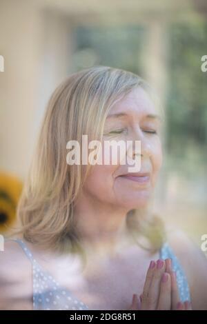 Serena mujer mayor orando con las manos apretada en la ventana
