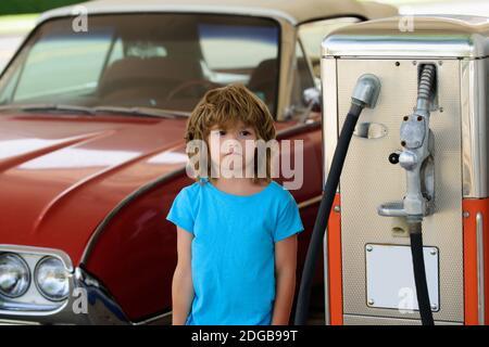 Niño en la gasolinera. Esperando combustible. Un niño que alimenta un coche retro en la gasolinera. Repostar con gasolina. Industria y servicio de la gasolina