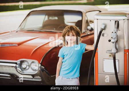 Gasolinera retro. Sonriente niño en la gasolinera. Esperando combustible. Niño que alimenta el coche de época en la gasolinera. Repostar con gasolina.