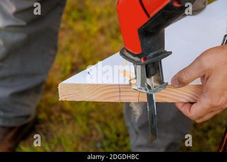 Mano de madera de primer plano con sierra de calar profesional, tablero de madera cortado, tablón de sierra