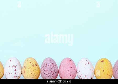 Divertido borde de Pascua para niños. Tarjeta de Pascua con huevos de colores sobre fondo azul claro. Espacio de copia. Primer plano. Huevos blancos de color amarillo rosa para el tratamiento de Pascua.