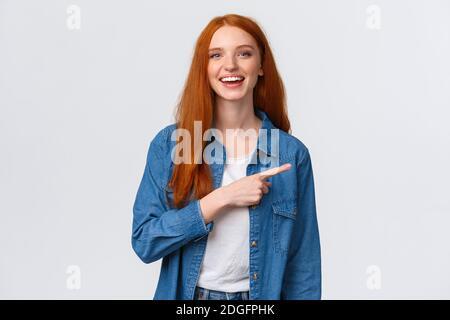 Despreocupada, amable y feliz mujer saliente pelirroja en camisa de denim, apuntando con el dedo a la derecha y riendo con cámara de la escariante