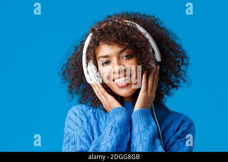 Primer plano retrato hipster atractiva mujer afroamericana con peinado rizado, ponerse los auriculares y sonreír, disfrutar de la música, Foto de stock