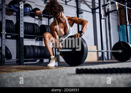 Una mujer atlética fuerte que se prepara para el entrenamiento de levantamiento de pesas