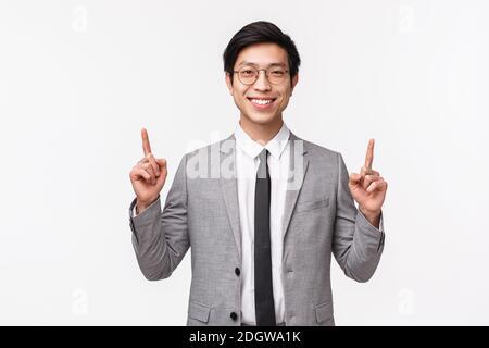 Retrato de cintura arriba de un exitoso hombre de negocios asiático sonriente en traje gris, apuntando con los dedos para mostrar el anuncio, presentando di