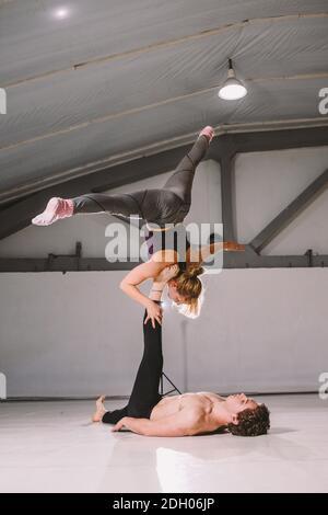 Deporte temático y un estilo de vida saludable. Acrobacias y acroyoga. Joven pareja deportiva practicando el soporte de mano de acroyoga. Hombre y mujer