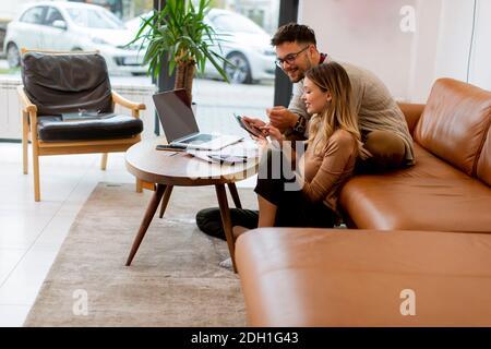 Una pareja joven guapa usando el portátil juntos mientras se sentaba en el sofá en casa Foto de stock