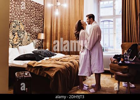 Vista lateral de una pareja romántica abrazando mientras está de pie junto a la cama en la habitación del hotel