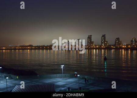 Vista nocturna del río Támesis en Londres con un banco de niebla detrás de altos edificios de apartamentos Foto de stock
