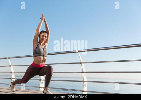 Imagen de una mujer sana y en forma física trabajando sola cerca del mar. Deportista estirándose antes de correr, haciendo ejercicio de calentamiento