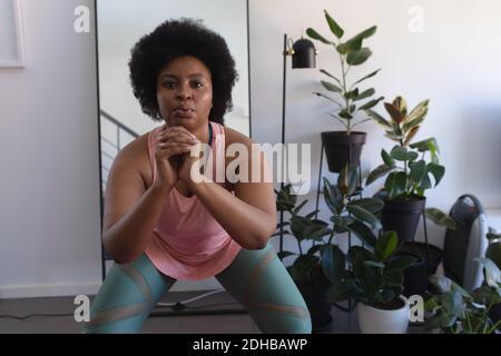 Retrato de una mujer afroamericana en el ejercicio de la ropa deportiva. Auto aislamiento de la aptitud en casa durante la pandemia de coronavirus covid 19.