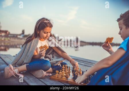 Dos pequeños amigos, niño y niña que se divierten mientras juegan al ajedrez sentado al lado del lago por la noche. Los niños están jugando. Amistad. Enfoque selectivo.