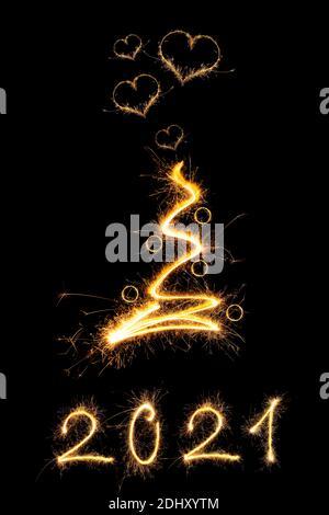 Resumen relámpago brillante árbol de Navidad con bolas de Navidad y destellos en forma de corazón aislados sobre fondo negro. Navidad mágica. PF2021.