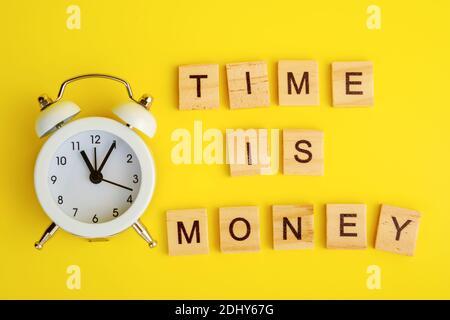 El texto de la hora es el concepto de dinero con reloj despertador y de madera cubos de bloque