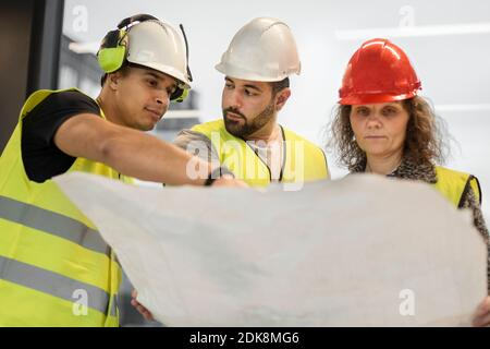 Trabajadores revisando el proyecto en el sitio de construcción