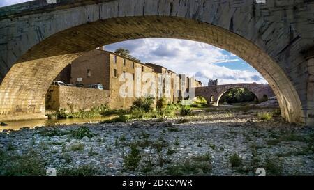 Vista de Lagrasse y el Pont de l'Alsou y Pont de l'Abbaye, monumentos culturales franceses, sobre el río L'Orbieu en verano. Además beaux Villages de France.