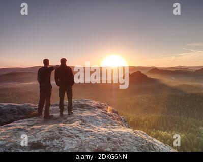 Los excursionistas y amigos permanecen en Cliff dentro del amanecer de ensueño y el pensamiento. Fogy paisaje de ensueño azul brumoso amanecer en un hermoso valle abajo