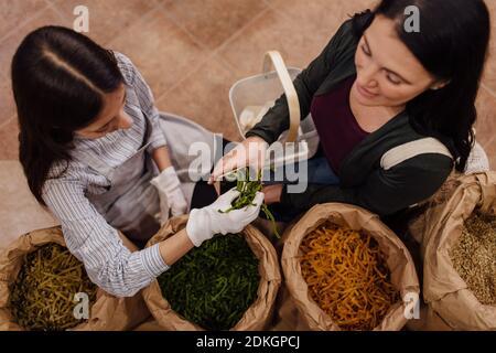 Vista superior de la mujer que compra comida casera en la tienda libre de paquetes. Vista de gran ángulo del asistente de la tienda poniendo pasta verde fresca en una bolsa de papel para el cliente en la tienda de comestibles.