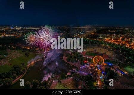 Panorámicas aéreas ciudad vista con brillantes luces de fuegos artificiales en la noche de Munich, hechas desde la torre olímpica.