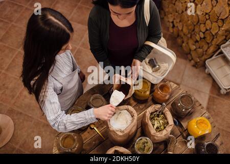 Vista de gran ángulo del asistente de la tienda que recoge harina para el cliente en la tienda libre de envases. Compras sin residuos - mujer que compra hierbas frescas y especias en el paquete de tienda de comestibles gratis.