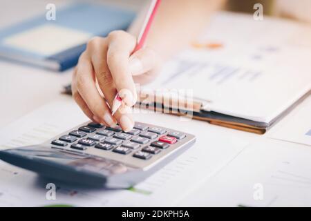 Primer plano de la contabilidad o del inspector financiero manos de hacer informe, calcular o comprobar el balance.inversión, economía, ahorro de dinero o concepto de seguro Foto de stock