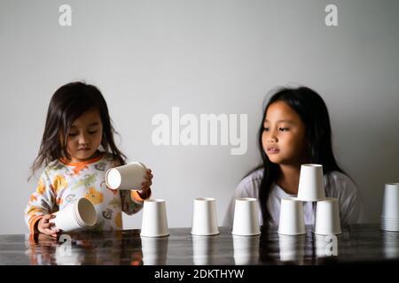 Niños jugando con copas de papel blanco Construyendo una torre de la copa en la mesa. Hermanos jugando juntos.