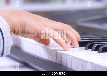 Primer plano de manos de niños tocando el piano en casa