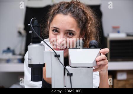 Joven científica mirando la cámara y sonriendo al lado de un microscopio en un laboratorio. Concepto de investigación de laboratorio.