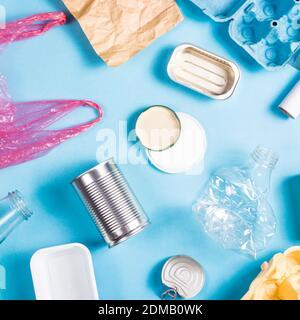 Concepto de basura de ordenación. Diferentes tipos de materiales para procesar sobre fondo azul: Hierro, polietileno, plástico, vidrio, lana, papel. Vista superior, disposición plana