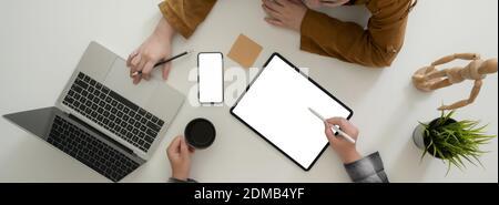 Imagen general de la consultoría de empresarios sobre su estrategia empresarial con dispositivos digitales simulados en una mesa blanca