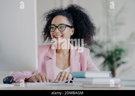 Foto de feliz rizado profesional gerente centrado en la pantalla de ordenador, sonríe ampliamente, tiene pelo rizado, lleva gafas transparentes, traje elegante, poses en el escritorio en su gabinete, trabaja a distancia