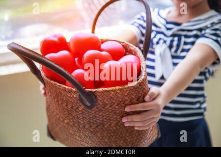 niña en azul marino vestido a rayas cesta de mano de corazones rojos representa ayudar a las manos, apoyo familiar, moral, pureza, inocencia, alegría, amor, hospitalidad, psicológico espiritual ancla concepto