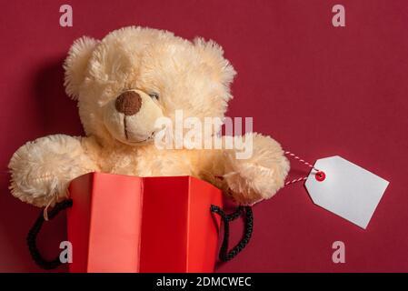 Oso de Peluche Juguetes en una bolsa de papel rojo con un vacío en una etiqueta blanca, sobre un fondo de papel rojo. Regalos de Navidad. Viernes negro en las ventas.
