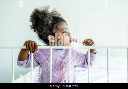 Africano americano lindo bebé niña sosteniendo comer helado cama en el dormitorio