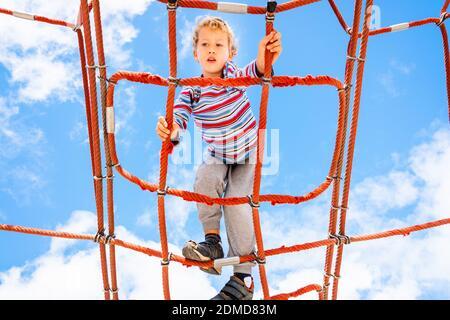 Muchacho rubio, encaramado en una web estructura de escalera de cuerda en un parque de juegos infantiles para la diversión de escalada.