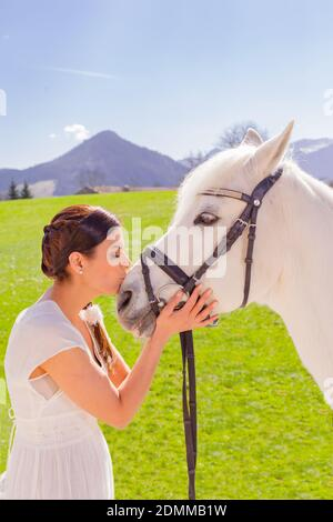Joven, hermosa mujer en el vestido blanco, besando la cabeza de su caballo blanco en el sol brillante en el campo verde Foto de stock