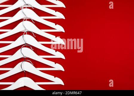 Imagen en color horizontal con vista frontal de perchas blancas sobre fondo rojo. Concepto de venta de ropa.