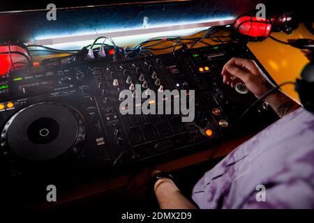 DJ juega live set y mezcla de música sobre la mesa giratoria en la etapa de la consola en el club nocturno. Disco Jokey manos en una estación de mezcla de sonido en el club fiesta. Mezcladora de DJ