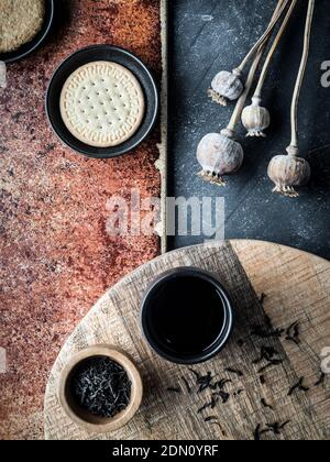 Different types of cookies and cup of cofee on grey and teracota background. Overhead shot.