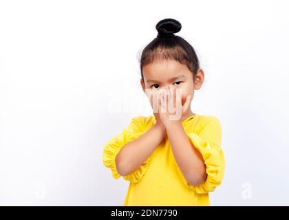 Retrato de una niña con las manos cubriendo la boca mientras se encuentra de pie contra el fondo blanco